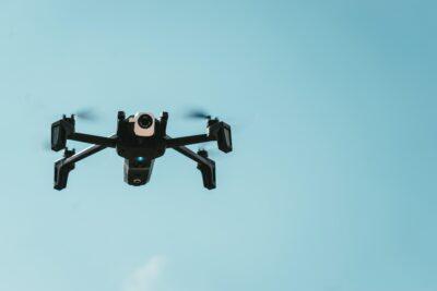 black drone flying on sky